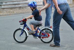 Man holding a child on a bicycle.