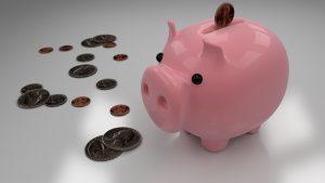 Coins around a piggy bank.