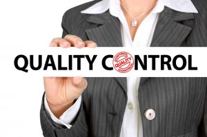 The close up of a woman holding a sign that says quality control.