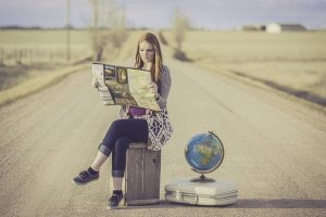 A woman with a suitcase, map and a globe ready for international office moving.